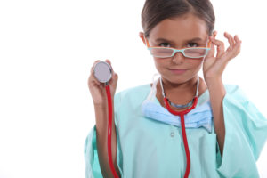 Child wearing grown up hospital scrubs, glasses and a stethoscope